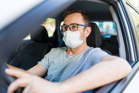 Portrait of man wearing surgical mask while driving a car.