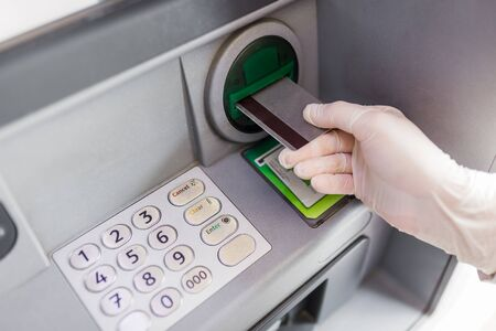 Close up of female hand wearing protective surgical glove and putting credit card into atm machine. Coronavirus concept. Banque d'images