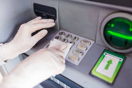 Close up of hands wearing protective medical gloves cleaning numeric atm keyboard with wet wipe. Public disinfection and coronavirus pandemic.