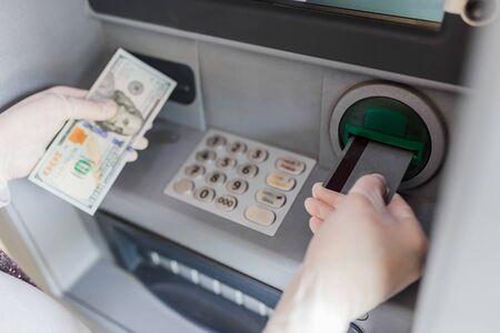 Client portant des gants médicaux et retirant de l'argent de la carte de crédit au guichet automatique à l'extérieur. Notion de coronavirus.