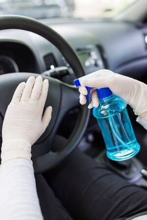 Driver wearing surgical protective gloves while spraying disinfectant on car steering wheel to prevent infection.