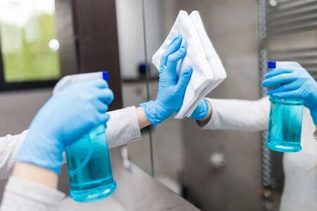 佩带防护手术手套的妇女清洗镜子在卫生间里。冠状病毒保护预防。