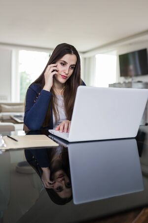 Businesswoman talking on the smartphone and using laptop at home. Remote working concept. Foto de archivo