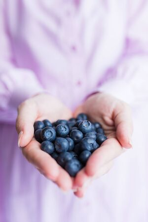 Healthy eating, vegetarian food and people concept - close up of young woman hands holding blueberries