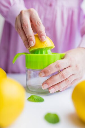 Female hands squeezing fresh lemon with plastic squeezer, healthy lifestyle concept.