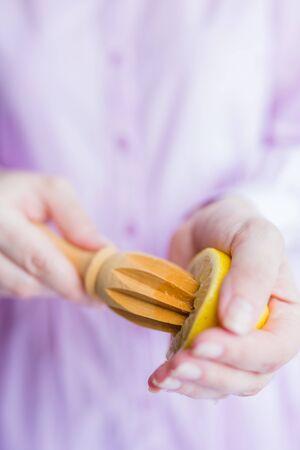 Female hands squeezing fresh lemon juice with wooden reamer, lemonade concept.