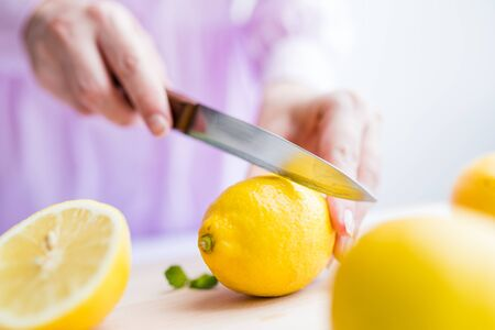 Close up of female cutting fresh lemon on wooden board at the table. Stock Photo