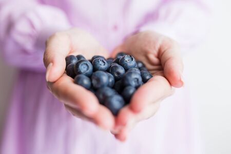 Close up of female hands holding tasty ripe blueberries. Space for copy.