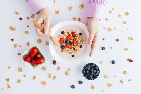 Flat lay of woman eating fresh muesli with fruits on table.