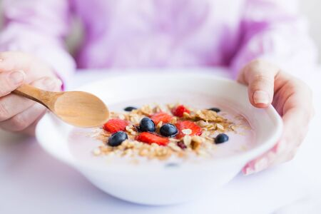 Close up of young female having healthy meal breakfast with cereals, strawberries and blueberries Stock Photo - 149686444