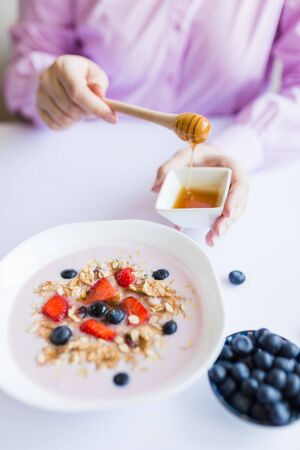 Female hand adding honey to oatmeal with fruits. Stock Photo - 149686189