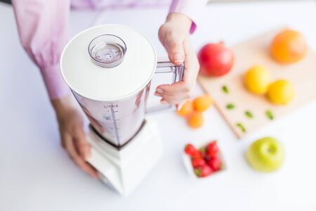Close up of female using blender and making fruit smoothie at home. Stock Photo