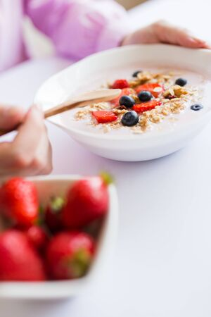 Close up of young female having healthy meal breakfast with cereals, strawberries and blueberries