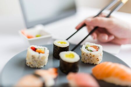 Asian sushi set with laptop and female hand holding chopsticks. Healthy meal at work food delivery concept. Stock Photo