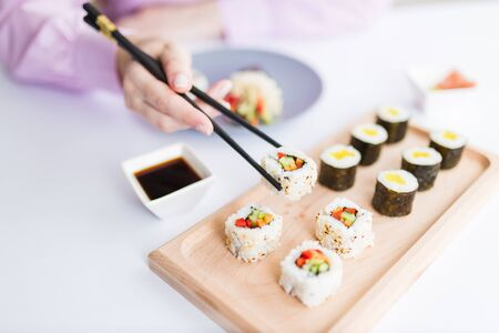 Woman hand taking piece of sushi roll with chopsticks. Healthy seafood asian japanese dish. Stock Photo - 149865354