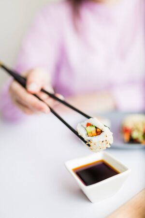 Female dipping tasty sushi roll with chopsticks into bowl with soy sauce at the table.
