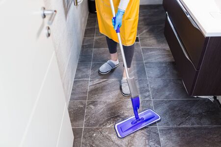 Maid doing chores at home by holding mopping stick. Coronavirus prevention concept. Stock Photo - 149894158