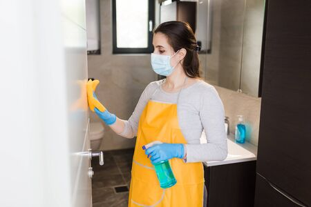Woman housekeeper wipes the door with rag and using spray disinfectant. Stock Photo - 149894160