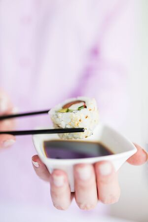 Close up of woman holding bowl with soy sauce and chopsticks with sushi roll, japanese traditional healthy meal concept. Stock Photo