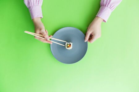 Flat lay of female hand holding chopsticks and one sushi roll on plate isolated on green background. Stock Photo