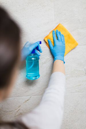 Young woman cleaning ceramic tiles with rag and spray disinfectant in bathroom. Stock Photo - 149894194