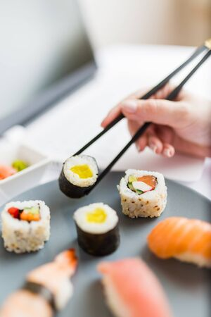 Businesswoman eating sushi next to her laptop. Take away japanese food and online order concept.