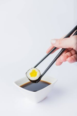 Close up of woman holding chopsticks with sushi roll and bowl with soy sauce on table, japanese traditional healthy meal concept.