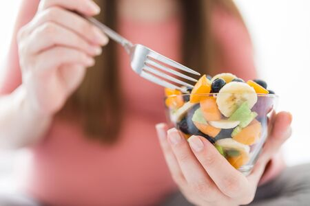 Close up of pregnant woman sitting on bed and eating fruit salad. Healthy meal concept. Stock Photo