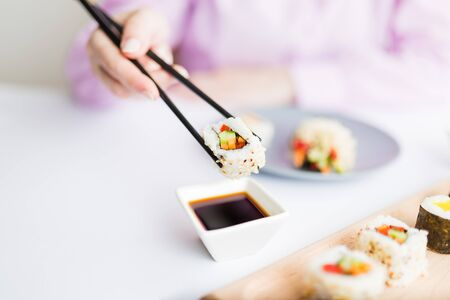 Close up of woman holding sushi roll with chopsticks above bowl full of soy sauce. Healthy traditional japanese meal concept. Stock Photo - 150029174