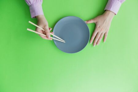 Flat lay of female hand holding chopsticks and empty plate isolated on green background.