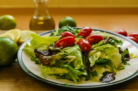 Fresh salad from different types of greens and cherry tomatoes, seasoned with olive oil and lime juice with lemon
