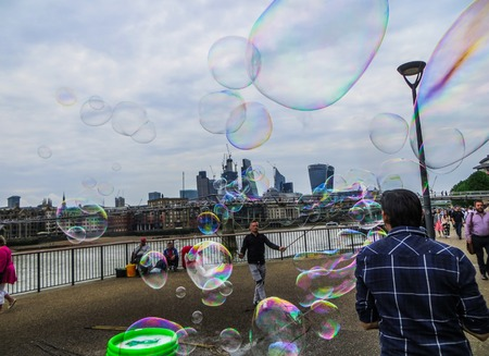 A young man blows soap bubbles on the Thames