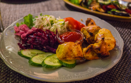 Grilled chicken fillet skewers on a plate, along with vegetables.