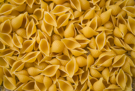 Pasta from hard wheat varieties, scattered on the table. Reklamní fotografie
