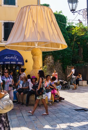 . Decorative lampshade in the form of a bench for people.People walking on old town street in Kotor, Montenegro.September 25, 2018