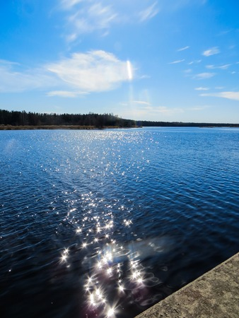 Dark blue water on the Lielupe River with glare from the bright sun in Latvia in early spring. Stock Photo