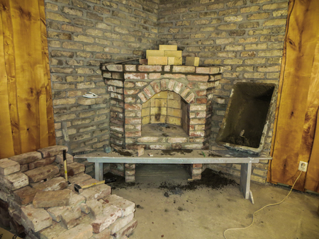 Building a fireplace in a house using old bricks. Beautiful bricklaying