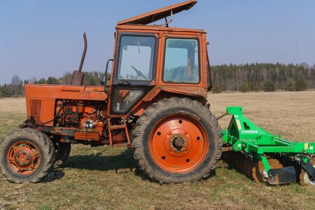 Old tractor for carrying out agricultural work in a field on a farm
