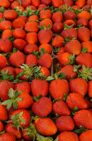 Fresh, fragrant strawberries in trays at the farmers market Banco de Imagens