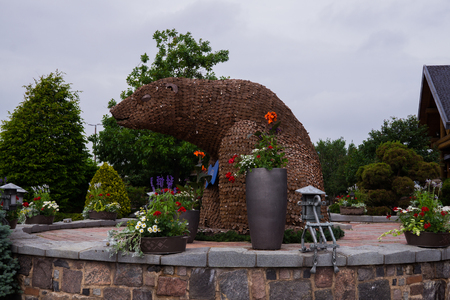 Riga, Latvia - July 5, 2019. Lido - a popular local restaurant stylized as an old mill. A bear sculpture from wooden circles 新聞圖片