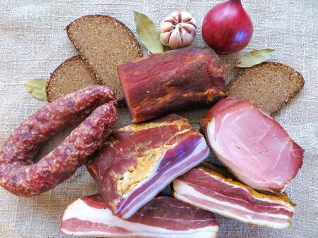 Raw smoked meat, ham and sausage, cooked according to traditional recipes, along with bread