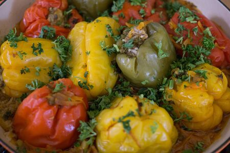 Red and yellow bell stuffed paprika peppers with meat with greens
