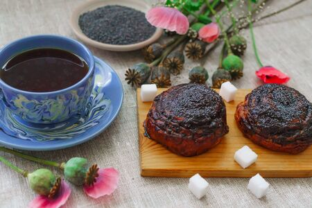 a fine breakfast, a mug of tea, fresh rolls with poppy seeds and poppy flowers