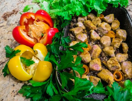 Stewed in the oven pieces of beef, decorated with greens and sweet pepper