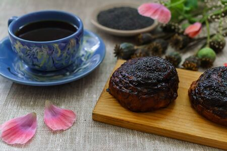A mug of black tea and buns with poppy seeds for breakfast