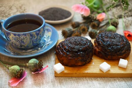 Sweet bun with flax seed and poppy and cup of tea on table