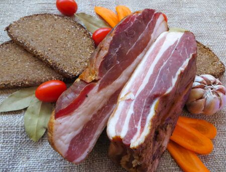 Raw smoked meat cooked according to old, traditional recipes, along with bread and vegetables 免版税图像