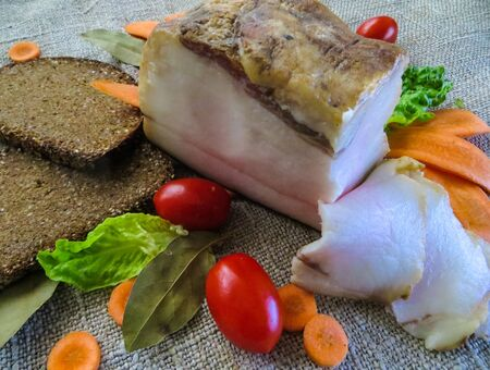 Salted tender fat cooked according to old, traditional recipes, along with bread and vegetables.