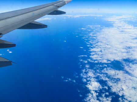 The plane flies over the ocean, surrounded by white clouds