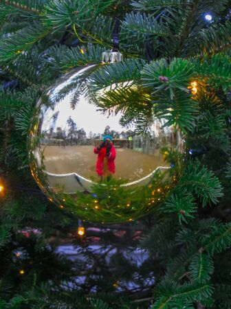 Big ball on a tree in the park, with a girl reflected in it Stock Photo